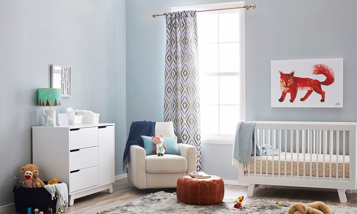 A boy baby nursery with blue walls, fox accent pieces, a leather ottoman, and a gray shag rug