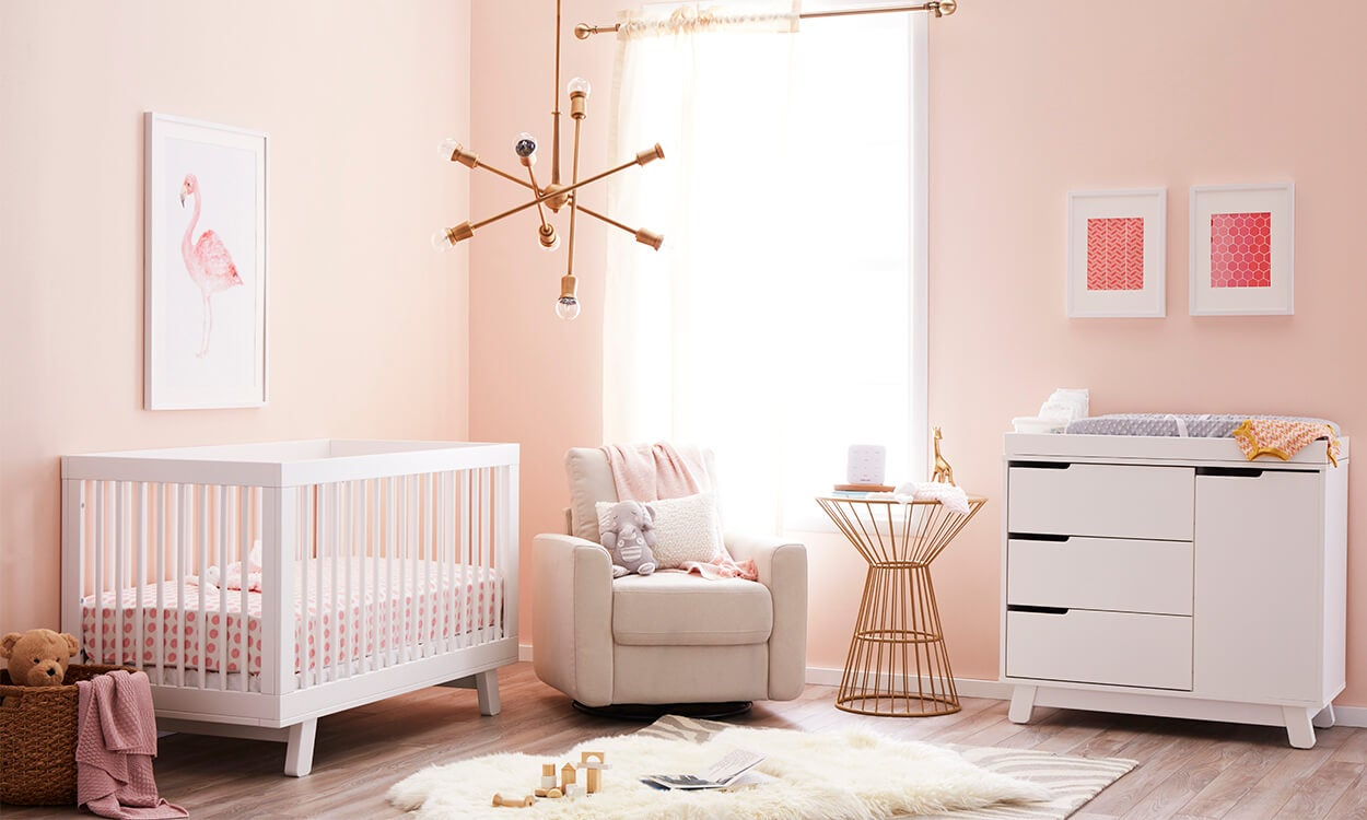 A girl baby nursery with pink walls, gold accents, and pink flamingo wall art