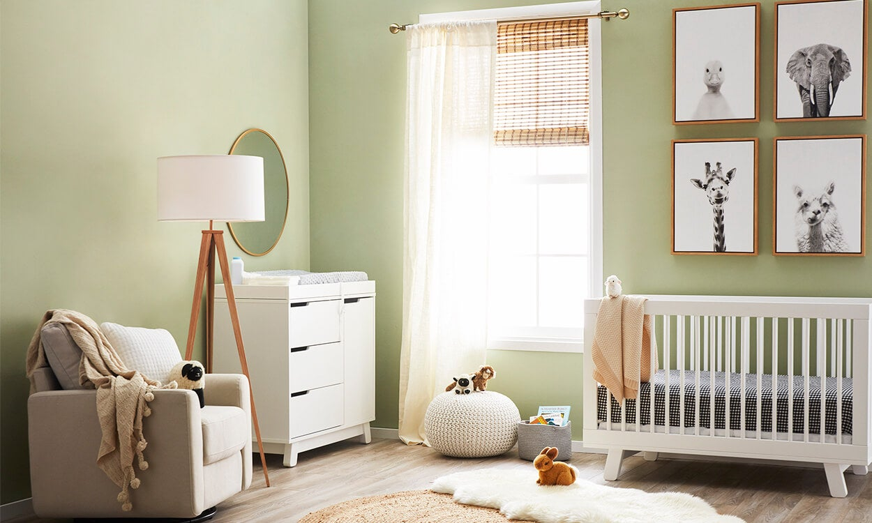 A gender neutral baby nursery with sofe green walls, and neutral colored baby furniture and accent pieces