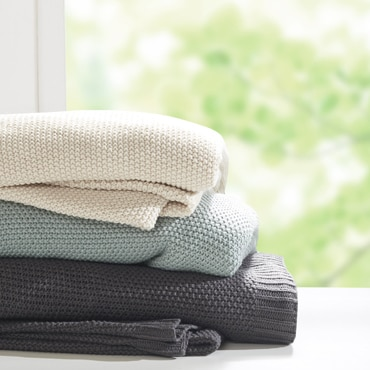 Three throws stacked on one another in white, teal, and grey
