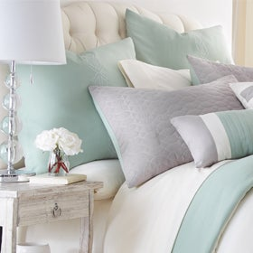 Close up of pillows on the bed in white, grey, and teal