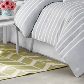 Close up of white and grey bed skirt on bed