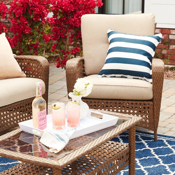 A closeup of patio furniture with stripped outdooor pillows
