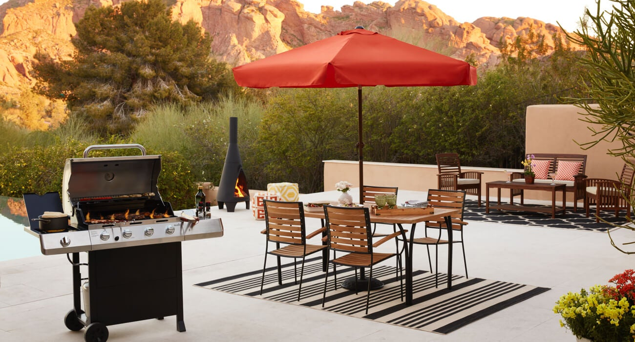 A backyard BBQ with a patio dining set, patio furniture, and a grill