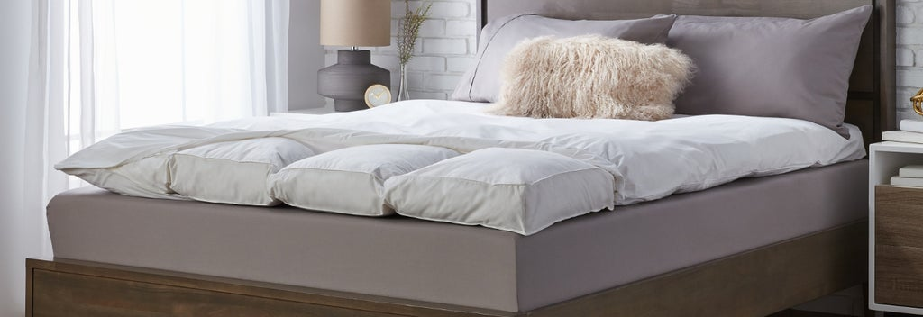 Featherbed topper on wood bedframe