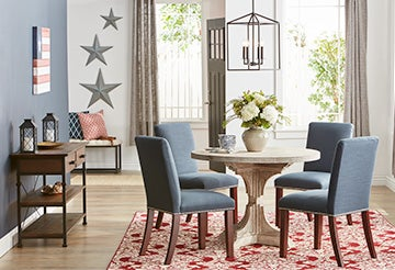 Dining room with round pedestal table, uphostered chairs and metal star wall decor