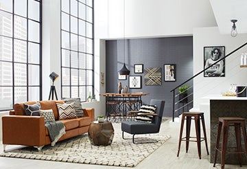 Modern, open-concept living room with leather couch and industrial metal accents