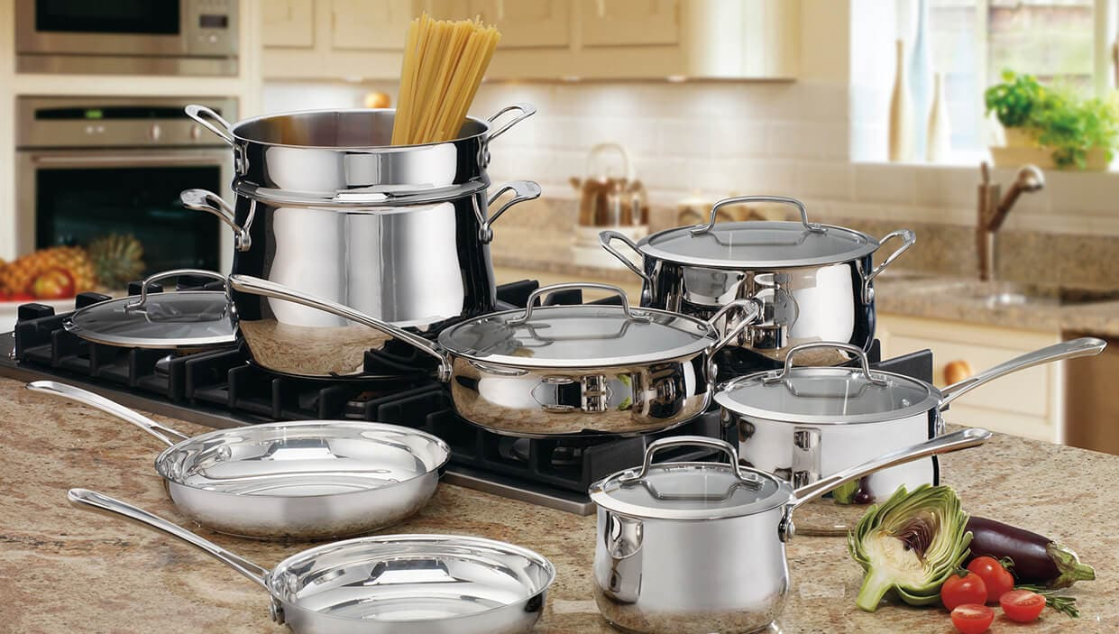 An assortment of stainless steel pots and pans on kitchen counter