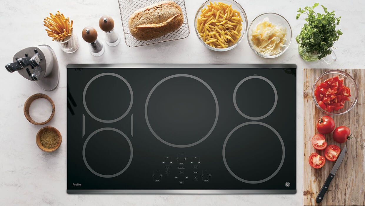 An electric smoothtop cooktop surrounded by cooking ingredients