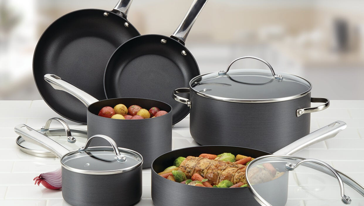 A set of black nonstick cookware in a kitchen with food in the pots.
