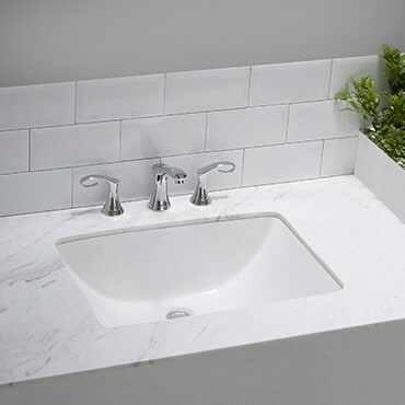 Close up of white poreclin sink set in marble countertop with a silver faucet