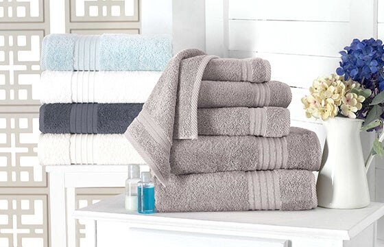 Stacked bath towels in gray, navy, white, and light blude