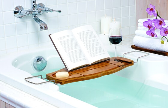 Bath tub caddie in a bath tub with book candles, and wine