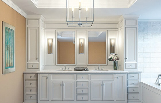 Bathroom vanity shown with three sconces and chandelier