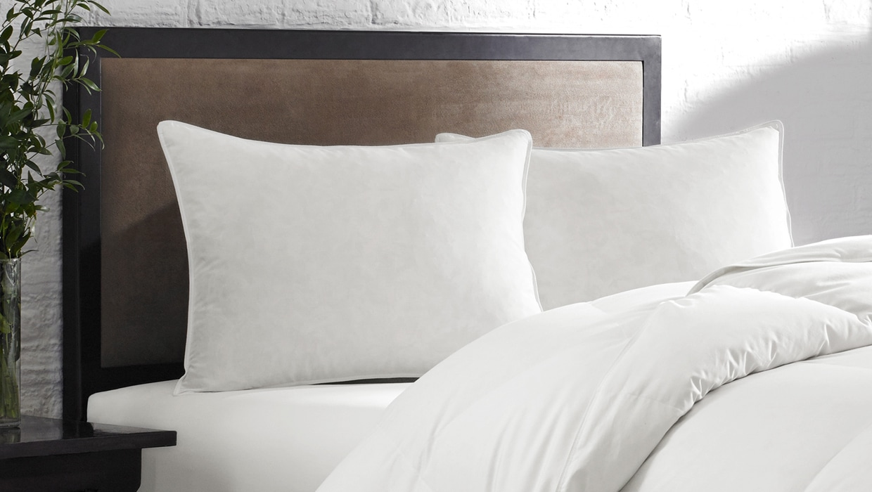 Close up of bed featuring two goose feather pillows