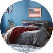 Bedroom with an American flag on the wall and a bed with red, white, and blue blankets