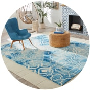 Beach house living room with a blue armchair beside an accent table on a blue rug