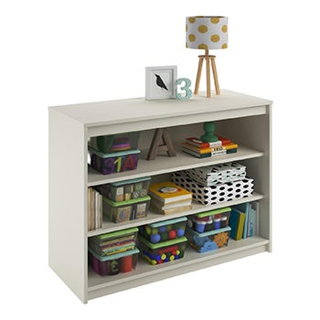 Small white bookcase filled with children's books and toys