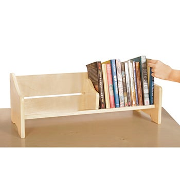 A natural wood table top book holder filled with books, a hand is reaching for a book