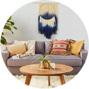 Living room with a gray sofa, a wooden coffee table, a faux fur rug, and decor in eclectic patterns