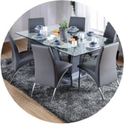 Contemporary dining room with a glass top dining table surrounded by stylish gray chairs on a shag rug