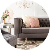 Glam sofas with pink throw pillows beside a polished end table
