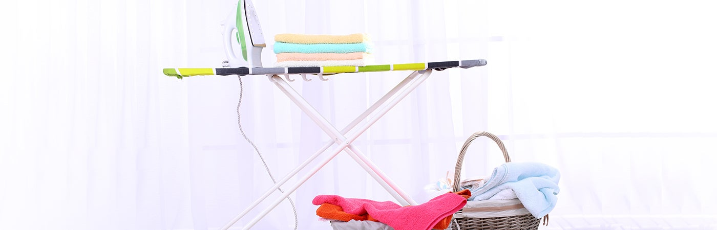ironing board with baskets full of clean laundry