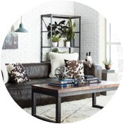 Industrial living room with a leather sofa, a mixed material coffee table, and a metal bookshelf