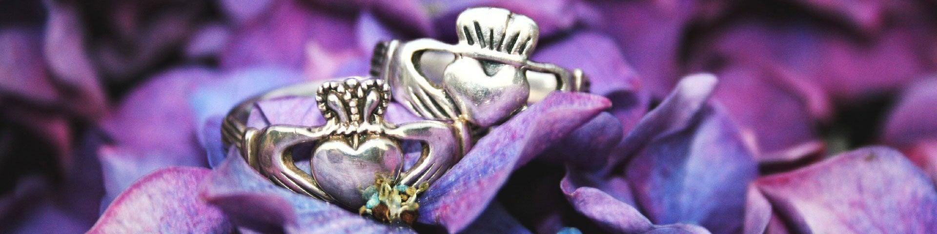 Two Claddagh rings on purple hydrangeas