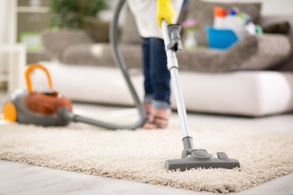 Woman Vacuuming a Carpet
