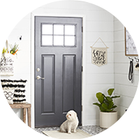 White entryway with a runner rug and a black door