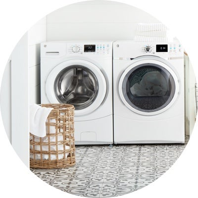 Washer dryer set in a white laundry room with a hamper