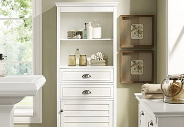 A white cabinet holding jars and other bathroom decorations