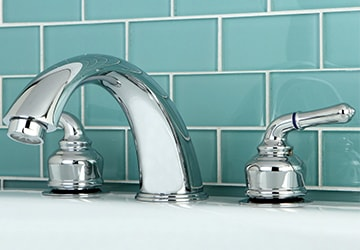Polished metal bathroom faucet against a turquoise tile wall