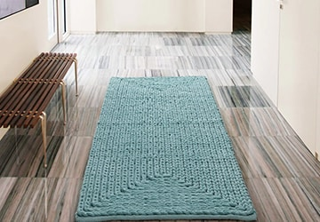Turquoise bathroom rug beside a wooden bench