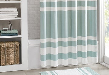 Striped shower curtain beside shelving full of bathroom accessories