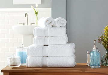 Stack of plush white body towels, hand towels, and face towels