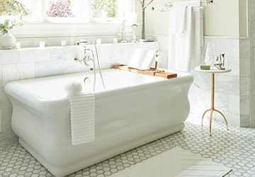 White porcelain tub beside a small table and a white rug
