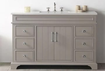 Gray vanity with a white marble top and polished drawer pulls