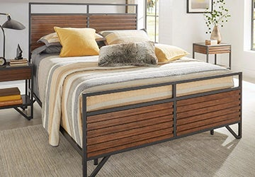 Metal bedframe with wood paneling and bedding in shades of yellow and gray