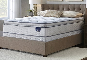 Thick mattress with a pillow top on an upholstered bed