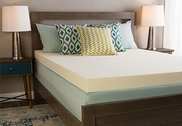 Memory foam mattress topper on a mattress in a teal sheet