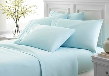 Blue sheets and pillowcases on a bed in a white bedroom