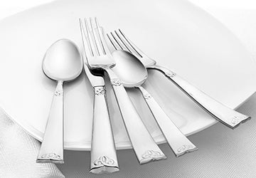 Silver knives, forks, and spoons arranged on a white plate