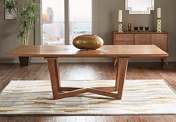 Wooden dining table with a golden centerpiece on an area rug