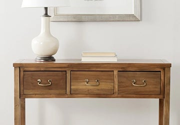 Wooden console table with metal drawer pulls and a table lamp