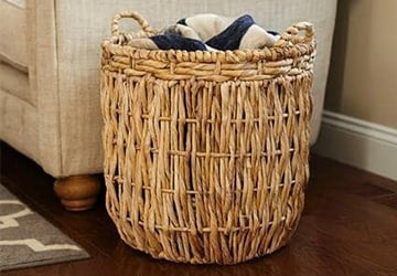 Wicker basket holding blankets beside a sofa