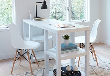 Practical white desk with two office chairs and a table lamp