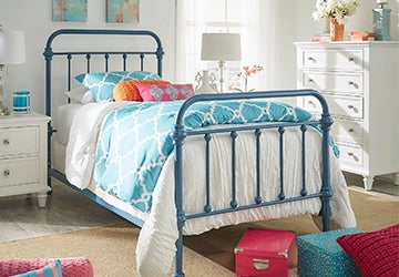 Old-fashioned kids' bed with a blue finish and colorful bedding