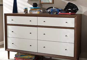 Brown dresser with white drawers in a kid's room